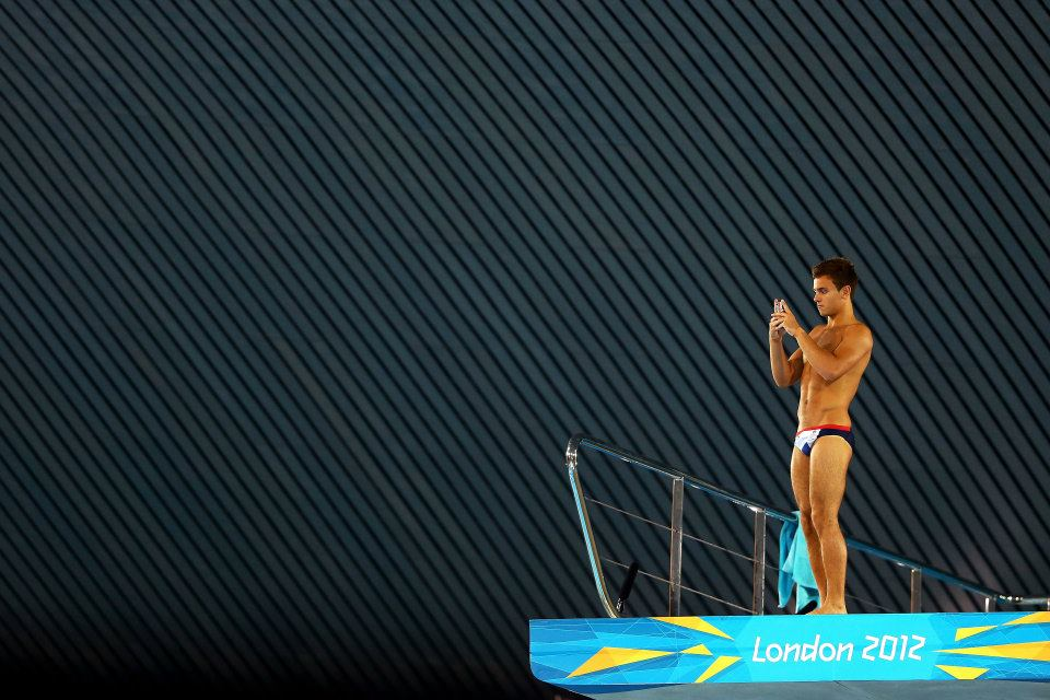 Tom Daley pauses to take a snap at the top of the Olympic Diving Board in London