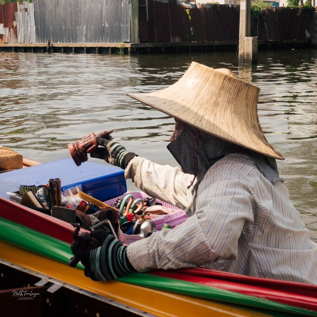 A floating market seller trying to sell us momentos of the trip