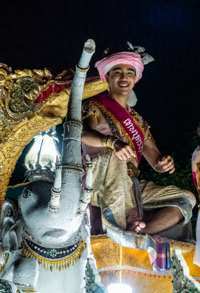 Smiling young Thai man sat aloft a float in the Loy Krathong parade in Chiang Mai