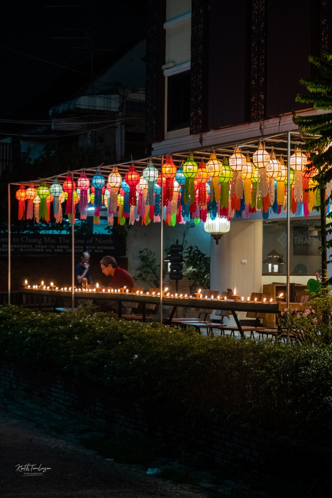 A diner enjoys the lamp light while he eats outside during the Loy Krathong celebrations.