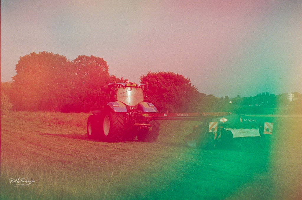 A colour washed photo of a tractor during harvest