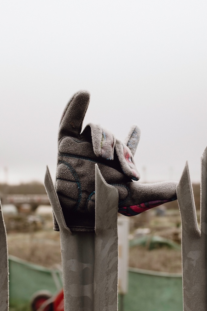An abandoned frosty glove left on a fence