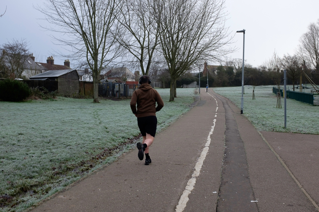 A man in shorts and sweater running in a frosty park