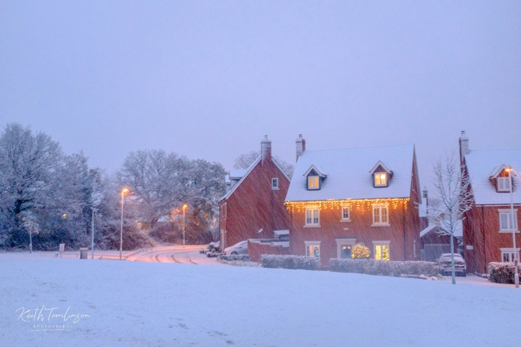 A snowy road and houses dressed for Christmas
