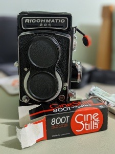 A photo of my Ricohmatic 225 and some Cinestill 800T film all ready to shoot