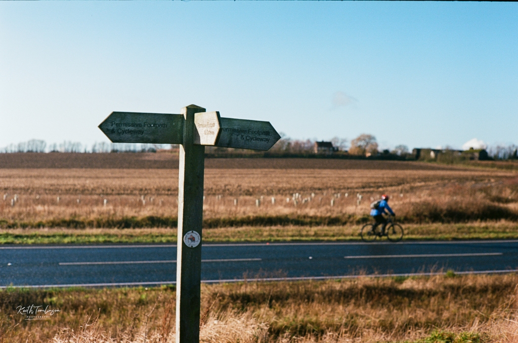 A signpost illustrating the local cycleways and a cyclist passing by in the background.