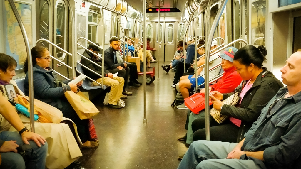 A photo taken on the subway in New York featuring a carriage full of people