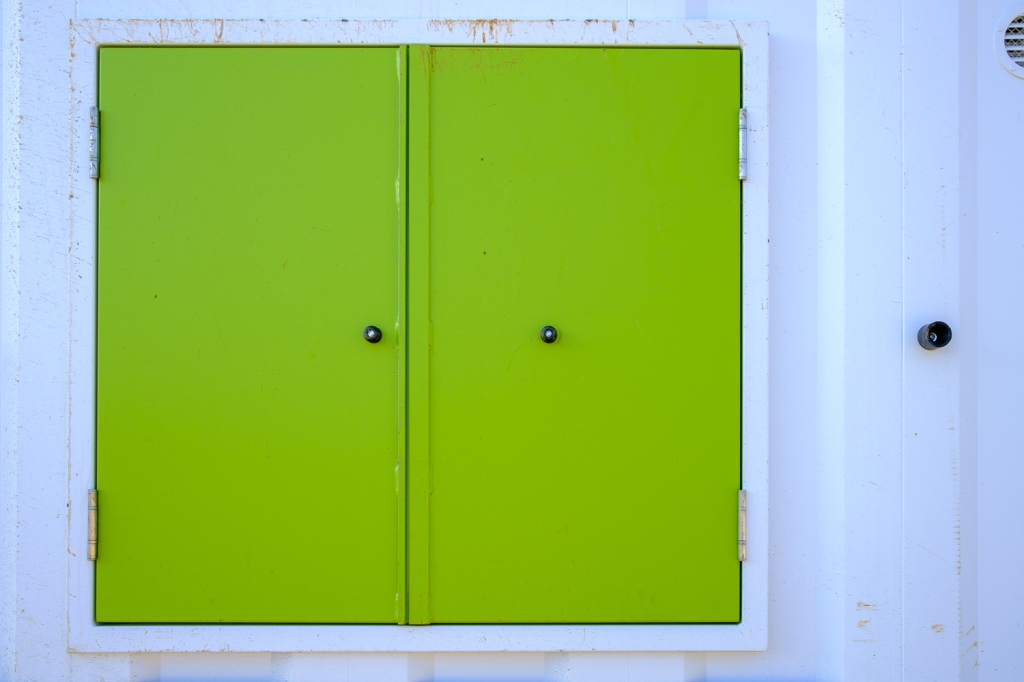 A bright green pair of doors are closed against a white metal hut