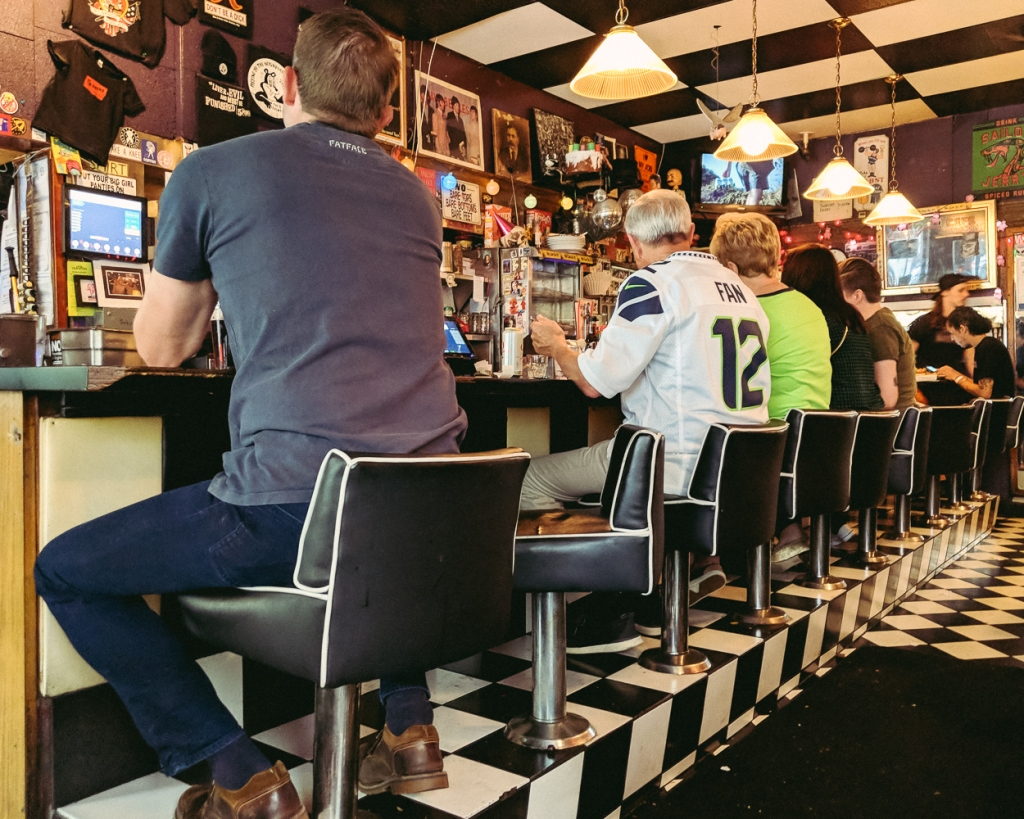 A row of patrons enjoying a bear at a bar in Seattle