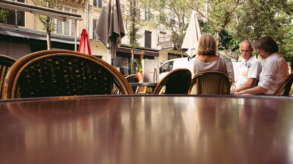 A group sit on the adjacent table outside a Parisian Cafe