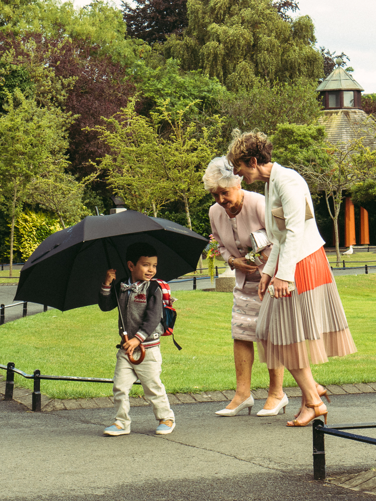 A young boy hides under an umbrella, teasing a couple of old ladies in a park