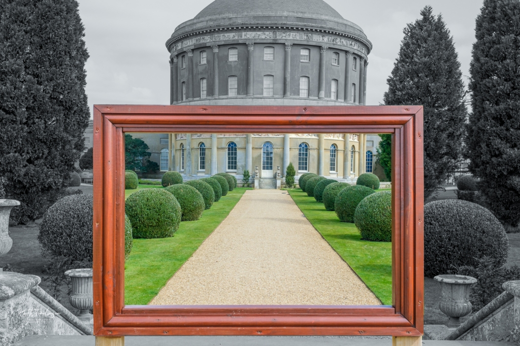 A view of Ickworth house through a wooden picture frame, the outside is in black and white and the view within is in full colour.