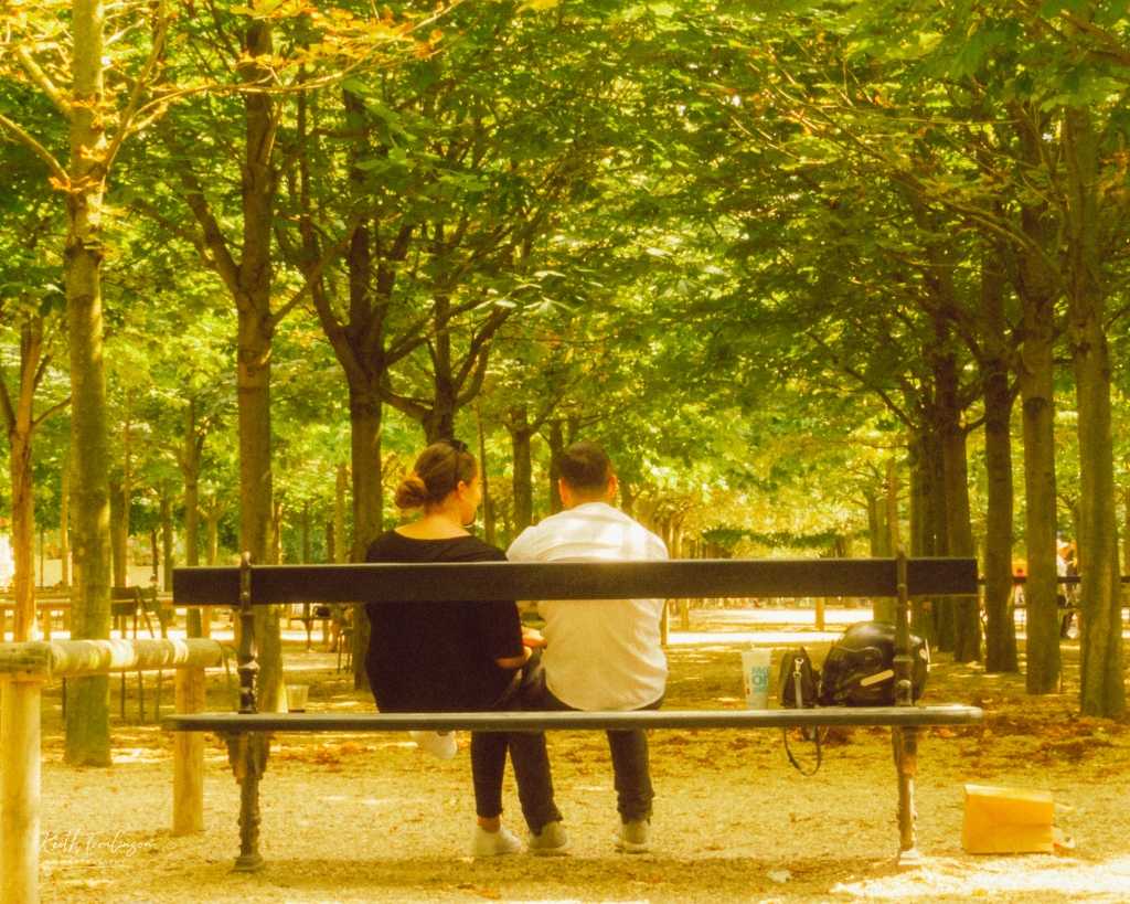 A young couple enjoy some spring sun in Jardin du Luxembourg, Paris
