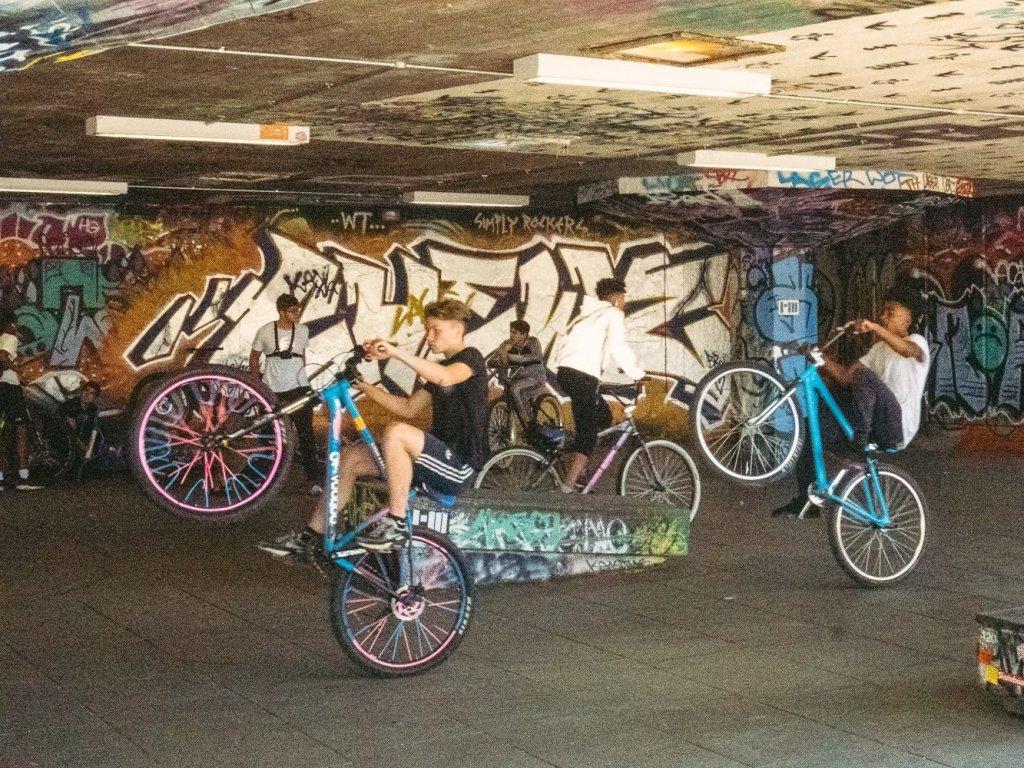 Two young men perform wheelies on mountain bikes in London