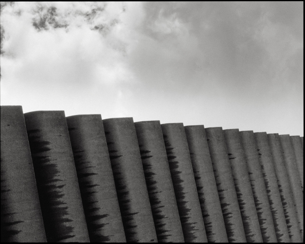 An image of concrete fins across a  black and white cloudy sky
