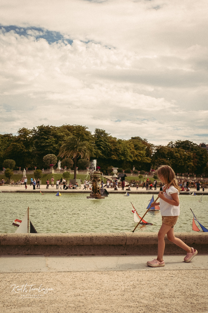 A girl pushing a boat along the fountain at the Jardin du Luxembourg in Paris