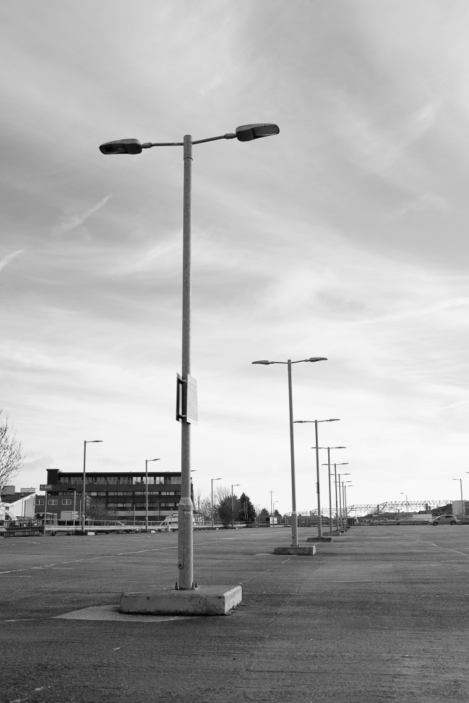A row of lampposts stand in a row and off into the distance