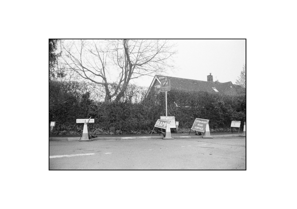 A black and white photo of a collection of various road signs littering a corner in Essex