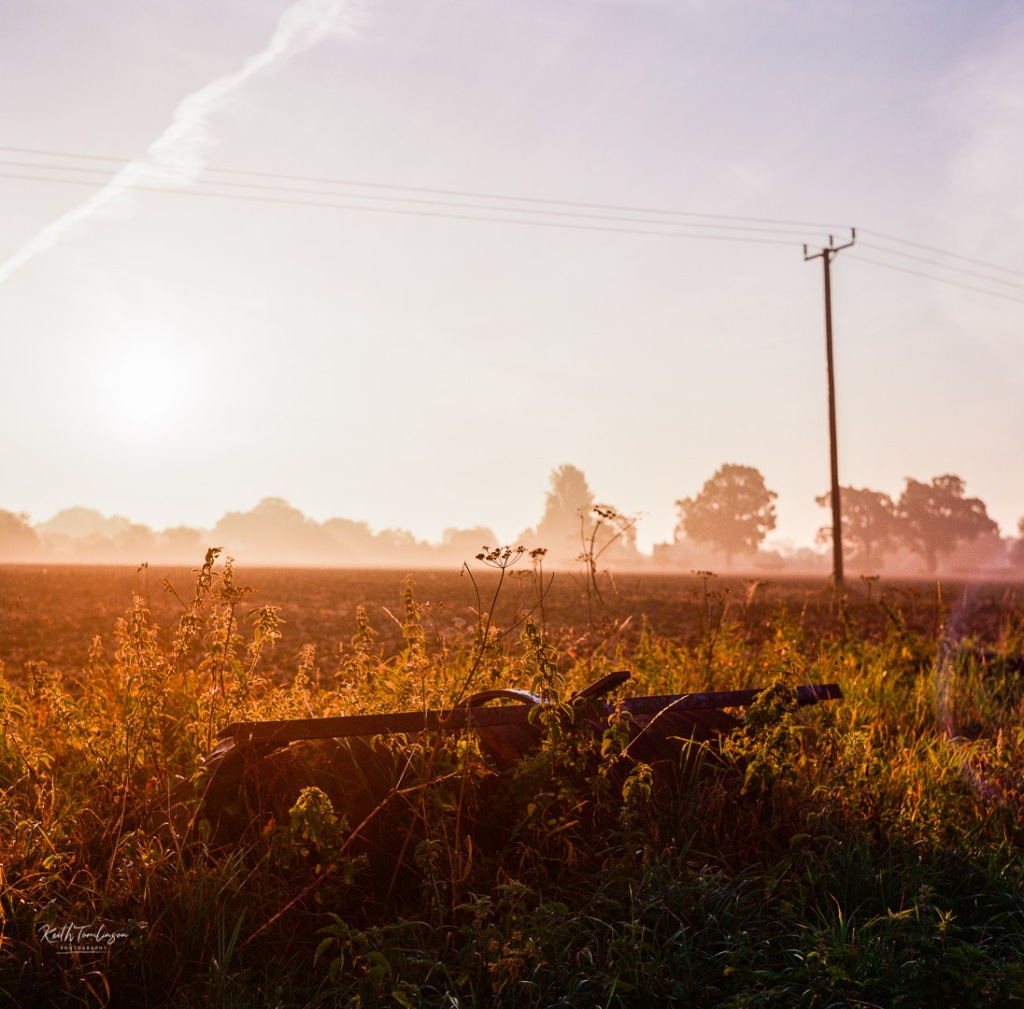 Sun rises over a ploughed field with a plough resting at  the edges of the field