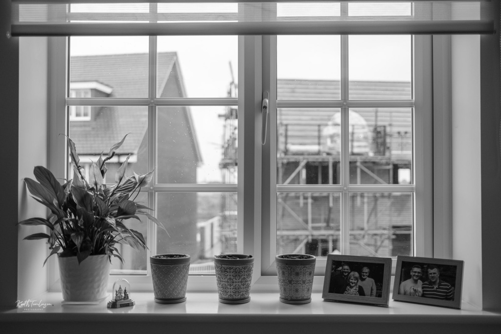 My office window sill featuring a Peace Lily (a moving in gift), some Buddhas from Thailand, three pots of spring bulbs and photos of me and my parents and me and my husband.  Beyond the ever changing view.